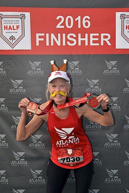 Sue Landa posing with race medals