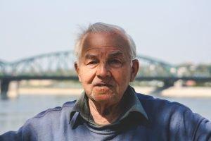 Older man near river with bridge