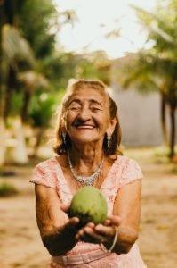 Happy Older Woman Holding Fruit