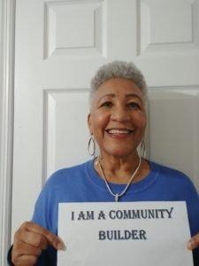 Volunteer Shirley Yearwood Holding Up Sign